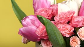 Bouquet flower with roses and tulips, on yellow, rotation, close up stock footage