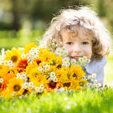 Bouquet of flowers. Happy smiling child with big bouquet of spring flowers lying on green grass Royalty Free Stock Images