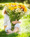 Bouquet of flowers. Сhild hiding behind big bouquet of spring flowers outdoors Stock Images