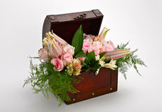 Bouquet of flowers. Bouquet of pink flowers in antique wooden chest Royalty Free Stock Image
