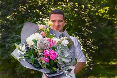 Bouquet of flowers as a gift! Portrait of a handsome young man royalty free stock photo