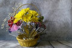 Bouquet of flowers in a basket on a gray background. Old uneven wall. royalty free stock photography