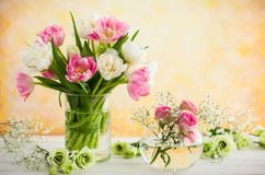 Bouquet of flowers. Beautiful flowers bouquet in vase on the wooden table.Tulips,roses and eustoma royalty free stock photo