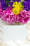Bouquet of flowers and a blank sheet of paper on wooden planks Stock Image