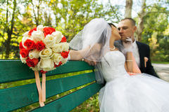 Bouquet of flowers with blurred newlyweds Stock Photo