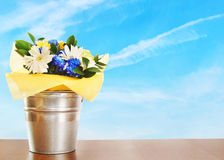 Bouquet of flowers in a bucket against blue sky Stock Photography