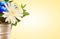 Bouquet of flowers in a bucket against yellow background Stock Photo