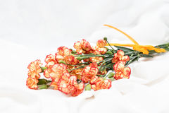 Bouquet of flowers. Bunch of carnation bloom. Orange yellow blooming blossom on the white fabric texture background. Royalty Free Stock Photography