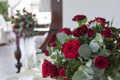 Bouquet of flowers in Burgundy tones in the foreground. Burgundy and red roses in the bouquet. Floristic. Celebration in the restaurant royalty free stock photo