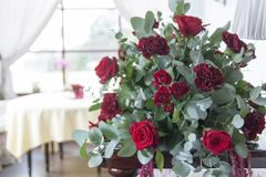 Bouquet of flowers in Burgundy tones in the foreground. Burgundy and red roses in the bouquet. Floristic. Celebration in the restaurant stock images