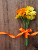 Bouquet from flowers of calendula with ribbon on wooden background Royalty Free Stock Photos