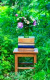 A bouquet of flowers of clover, cornflowers and Jasmine in a glass vase and a stack of books on an old wooden chair among the gree. N grass in the spring garden Royalty Free Stock Photography