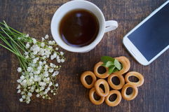 Bouquet of flowers and cup of tea on a wooden table with phone with a blank screen royalty free stock photos