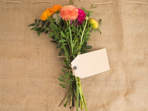 Bouquet of flowers with empty textfield. Beautiful bouquet of flowers with a blank textfield on jute fabrics Royalty Free Stock Image