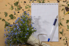 A bouquet of flowers forget-me, notebook and pen on the wooden t Royalty Free Stock Photos