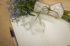 A bouquet of flowers forget-me, notebook and pen on the wooden t Royalty Free Stock Image