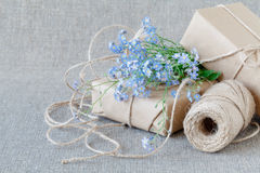 A bouquet of flowers forget-me-nots with gift Royalty Free Stock Photo
