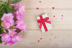 Bouquet of flowers with gift box on a wood Royalty Free Stock Photography