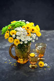 Bouquet of flowers in a glass jug and two glasses Stock Images