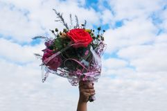 a bouquet of flowers in hand on blue sky background. royalty free stock photography
