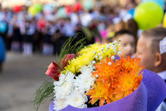 A bouquet of flowers in the hands of elementary school students. A ceremony in the school yard on the first of September stock image