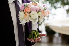 Bouquet of flowers in the hands of the groom stock images