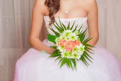 Bouquet of flowers in the hands of a young bride Royalty Free Stock Photography