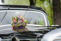 Bouquet of flowers on hood retro wedding car Stock Photos