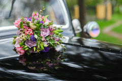 Bouquet of flowers on hood retro wedding car Stock Images