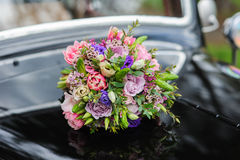Bouquet of flowers on hood retro wedding car Royalty Free Stock Photography