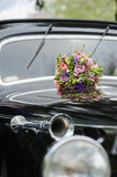 Bouquet of flowers on hood retro wedding car. Elegant bridal bouquet of different flowers on the hood of a black retro car. Lacquered surface reflection Royalty Free Stock Photography
