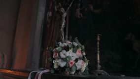 A bouquet of flowers lies near the statue of Jesus