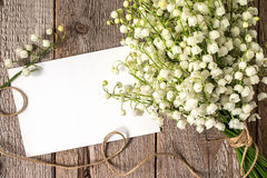 Bouquet of flowers lily of the valley and empty paper sheet. On  rustic table from above, beautiful vintage card, top view, copy space for text Royalty Free Stock Image
