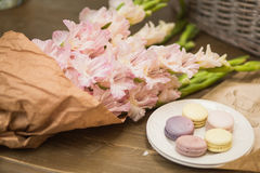 Bouquet of flowers and macaroons. Bouquet of pink gladioli in craft packing and a plate of macaroons on a wooden table Royalty Free Stock Photography