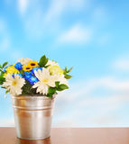 Bouquet of flowers in a metal bucket against blue sky Stock Photos