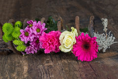 Bouquet of flowers in metal spring on grunge wood surface artist. Bouquet of flowers in metal spring on a grunge wood surface artistic conversion Stock Image