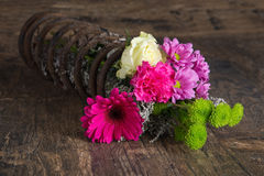 Bouquet of flowers in metal spring on grunge wood surface artist Royalty Free Stock Image