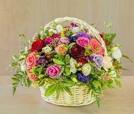 Bouquet of flowers, multi-colored roses in a wicker basket. A beautiful bouquet of flowers, multi-colored roses with green leaves stands in a wicker basket on a stock photo
