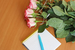 Bouquet of flowers and a Notepad with pen. Royalty Free Stock Images