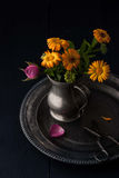 Bouquet of flowers in the old metal jug on the vintage tray Stock Image