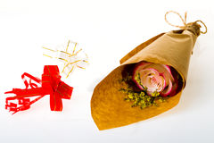 Bouquet of flowers in parchment and two colored bow of ribbons o Royalty Free Stock Photography