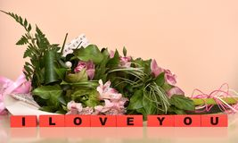 Flowers and red wooden blocks with I Love You message stock photography