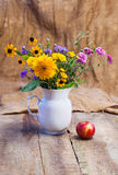 Bouquet of flowers and ripe red apple royalty free stock photography