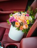 Bouquet of flowers roses luxury gift box in the car seat.  Stock Photo