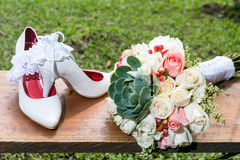 Bouquet of flowers and shoes for the bride on wedding day Stock Photo
