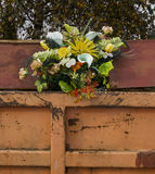 Bouquet of flowers sticking out from a trash container Royalty Free Stock Photo