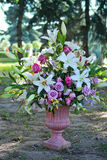 Bouquet of flowers in  stone vase in an exterior of city park Royalty Free Stock Photos