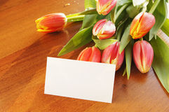 Bouquet of flowers on the table and empty card Royalty Free Stock Image