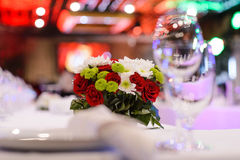 A bouquet of flowers on a table in a restaurant. Beautiful floral arrangement of roses, chrysanthemums and other flowers on the table for the banquet in luxury stock photos