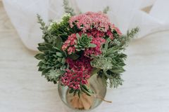 Bouquet of flowers in vase. Beautiful wedding bouquet of succulents, crimson sedum and field grass royalty free stock images